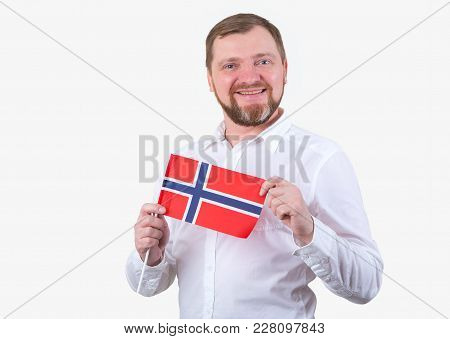 Adult Man With A Beard In A White Shirt Holds The Flag Of Norway.