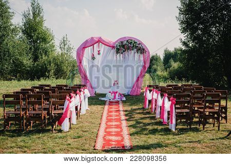 Wedding Arch And Chairs For Ceremony Decorated With White And Pink Fabric And Flowers
