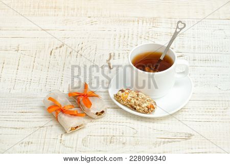 Cup Of Tea And Few Bar Of Muesli. White Wooden Background