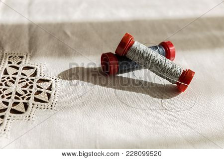 Two Spools Of Gray Thread On A Hand-embroidered Tablecloth