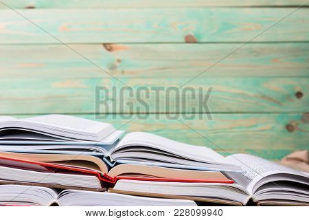 Stack Of Open Books Pile Of Various Books On Wooden Background. With Copy Space For Your Text