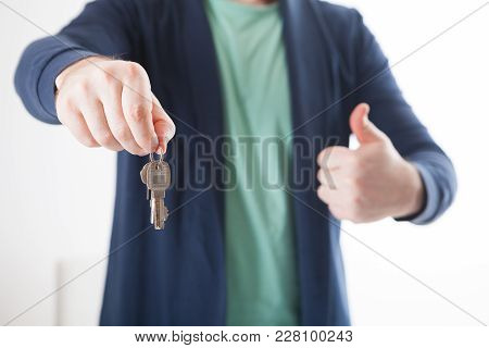 Bright Picture Of Man Hand Holding House Keys. Holding A Thumb Up