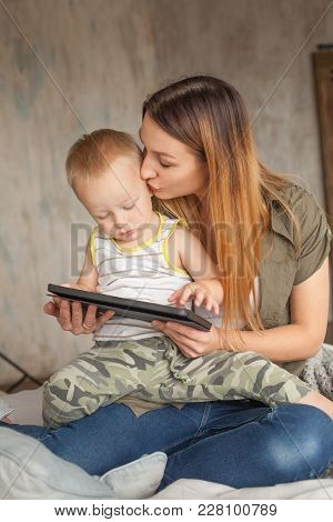 Funny Mom And Child Are Having Fun With Tablet. Young Mother And Her Son Play In Kids Room