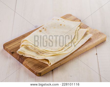 Armenian Flat Bread Lavash. Pita Bread On Wooden Cutting Board Over White Wooden Table. Copy Space.