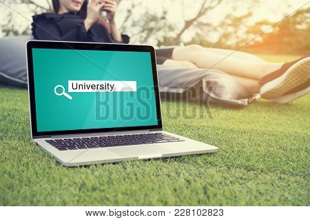 Searching University Background Concept On Laptop Screen With Asian Young Woman Sitting On Bean Bag