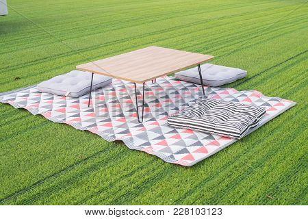 Wood Picnic Table And Bench Seat At Greensward In Morning.