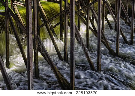 Among The Metal Structures Of The Old Dam, The Green Waters Of The River Foam And Bubble.