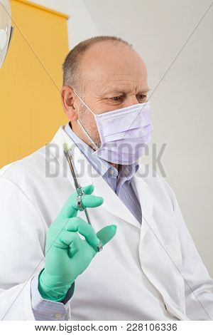Male Dentist With Mask Holding  Local Anesthetic Injection Preparing For Treatment