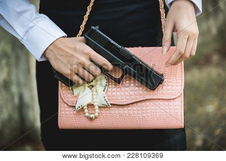 Young Woman With Concealed Weapon Gun In Her Small Handbag
