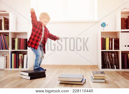 Three Years Old Child Playing Among Books At Home. Happy Boy Jumping In White Room