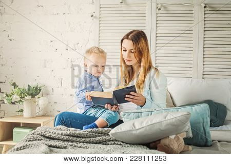 Pretty Young Mother Reading A Book To Her Son. Mom And Child Reading
