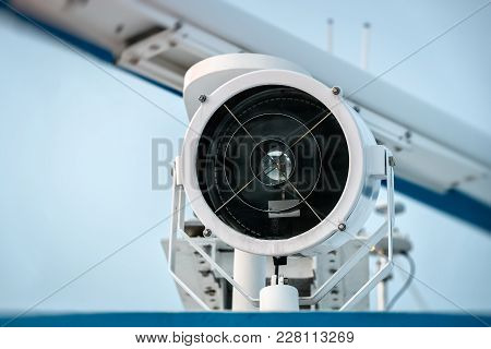 Searchlight On Top Of Ship Against The Sky. Closeup.