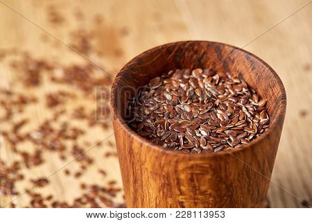 An Overturned Wooden Bowl With Linseeds On A Brown Rustic Wooden Background Seen From The Opening, C
