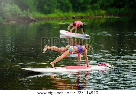 Young Athletic Woman Doing Fitness On A Board With A Paddle On The Lake, Training A Healthy Lifestyl