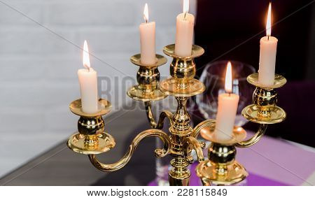 Glasses And A Candlestick On A Glass Table In A Restaurant. Romantic Setting. Microphones For Karaok