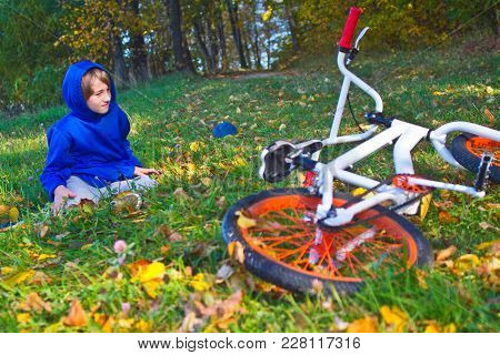 Boy Hurt After Falling Off His Bicycle. Sad And Unhappy Child Crying