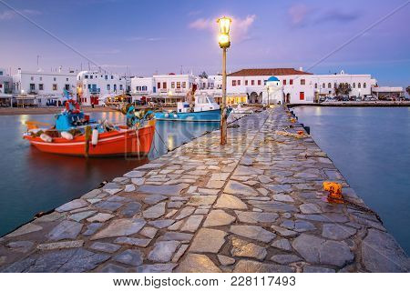 Pier With Fishing Boats, Church And Town Hall In Old Port Of Mykonos City, Chora, On The Island Myko