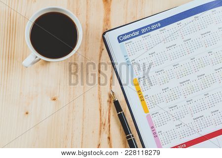 Calendar Planner With Fountain Pen And Hot Coffee On Wood Table.office Tool.
