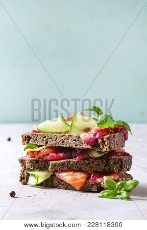 Sliced Beetroot Marinated Salmon Sandwiches With Rye Bread, Cucumber, Basil And Lemon Served In Stac