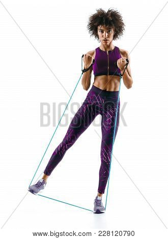 Young Girl Performs Exercises Using Expander. Photo Of Muscular African Girl Isolated On White Backg