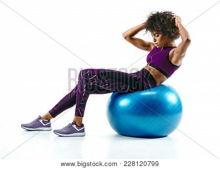 Young Woman Doing Abs Exercise On Fitness Ball. Photo Of African Girl In Silhouette On White Backgro