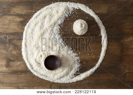 Raw Rice In A Pottery Scattered On A Table In The Shape Of A Yin Yang Sign