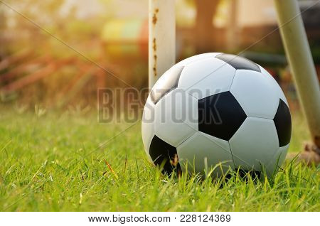 Football Or Soccer Ball On The Lawn With Morning Sunlight , Outdoor Activities.