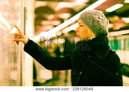 Casually Dressed Woman Wearing Winter Coat, Orientating Herself With Public Transport Map Panel, Poi