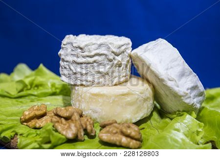 Cheese Of Three Varieties On A Plate With Lettuce Leaves And Walnuts (saint-remy, Crottin D Eyubonne