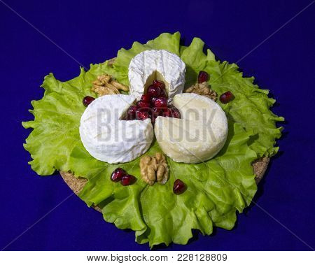 Cheese Of Three Varieties On A Plate With Lettuce Leaves, Pomegranate Seeds And Walnuts (saint-remy,