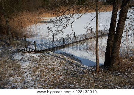 The Frozen River Bank, Snow Covered Footbridge, Trees, Rushes, Fallen Fields And Blue Sky With White
