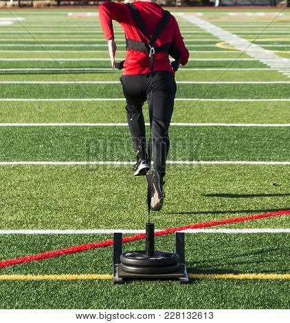 A Track And Field Runner Is Pulling A Weighted Sled Across A Green Turf Field For Speed And Strength