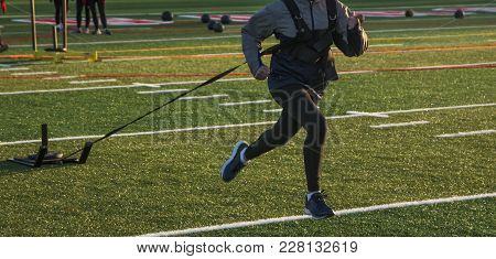 A Female High School Athlete Is Pulling A Sled With 25 Pounds Across A Green Turf Field During After