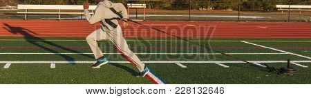 A High School Track And Field Sprinter Is Pulling A Weighted Sled Across A Green Turf Field With His