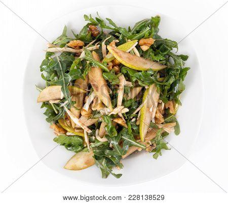 Arugula Pear And Walnut Salad Over White Background