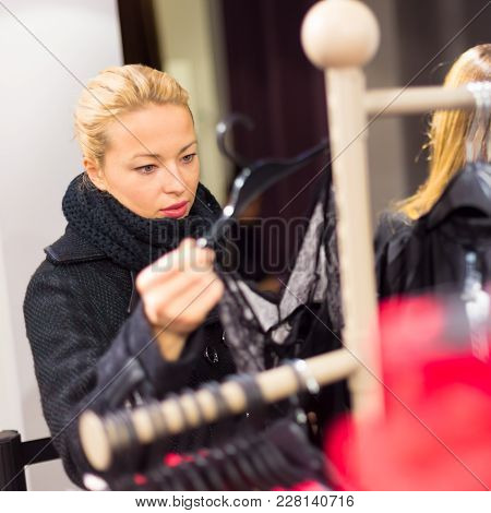 Woman Shopping Clothes. Shopper Looking At Clothing Indoors In Store. Beautiful Blonde Caucasian Fem