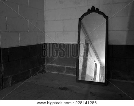 An Old Mirror Lying Against A Basement Wall Apparently Forgotten.