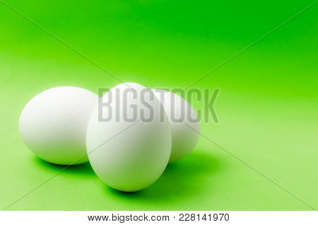 Three Chicken Eggs On A Bright Green Background.food Close Up.