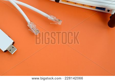 Internet Router, Portable Usb Wi-fi Adapter And Internet Cable Plugs Lie On A Bright Orange Backgrou