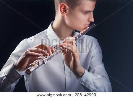 Young Man Playing The Flute On Black Background