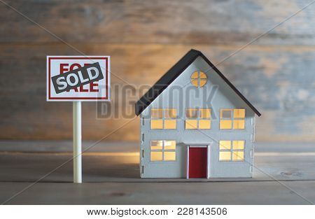 For Sold Sign Next To A Model House