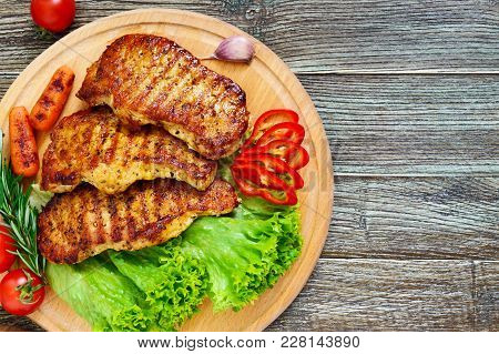 Juicy Steaks With Greens And Vegetables On A Wooden Tray. A Large Piece Of Pork Tenderloin Grilled.