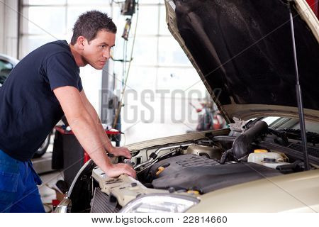 A young mechanic staring at a car, thinking