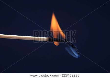 Burning And Smoking Wooden Match On Dark Background