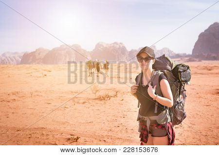Tourist Woman With Friends In A Desert. Jordan Natural Park Wadi Rum. Backpacker On The Road. Woman