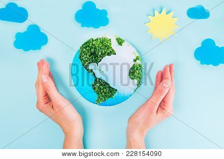 Top View Female Hands Holding Earth Paper And Green Sprouts Collage Model On Blue Background With Pa