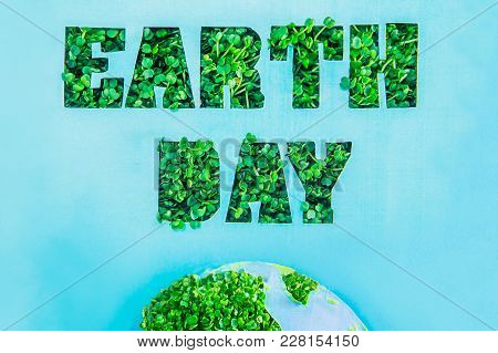 Creative Concept With Outline Lettering Earth Day In Green Fresh Grass Sprouts And Part Of Planet Mo