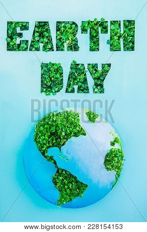 Creative Concept With Outline Lettering Earth Day In Green Fresh Grass Sprouts And Planet Model On B