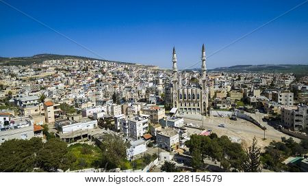 Aerial View Flying Over An Arab Cityscape Buildings And Streets, With View Of A Beautiful Mosque Wit