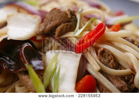 Udon Wok Noodles With Pork And Peppers, Close Up. Japanese Cuisine